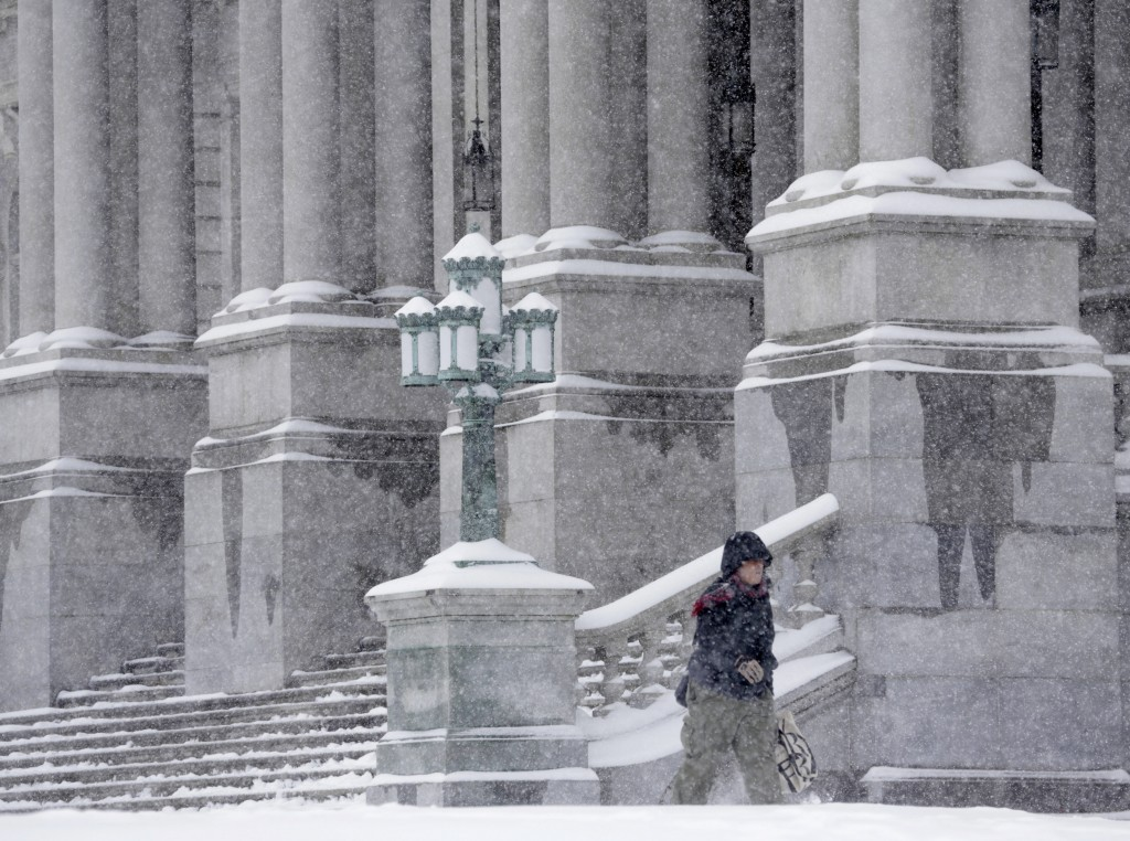 A pedestrian walks in the snow on Monday at the state Capitol in Albany. (AP Photo/Mike Groll)