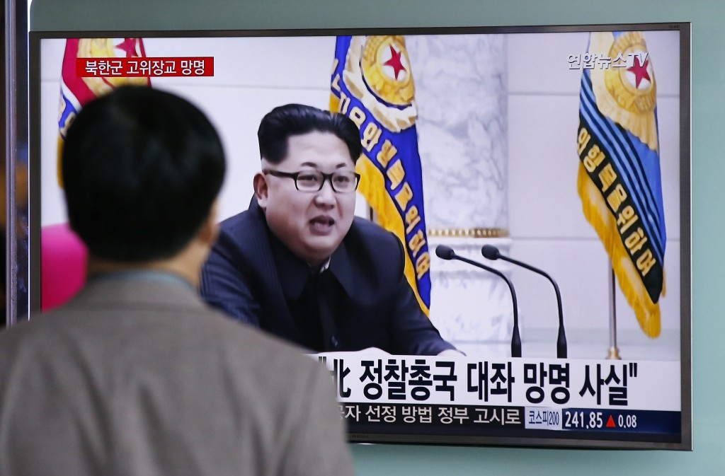 """A man watches a news broadcast showing file footage of North Korean leader Kim Jong Un at Seoul Railway Station in Seoul, South Korea, Monday, April 11, 2016. A colonel from North Korea's military spy agency fled to South Korea last year in a rare senior-level defection, Seoul officials said Monday. The letters read """"True, A colonel from North Korean military's General Reconnaissance Bureau Asylum."""" (AP Photo/Lee Jin-man)"""