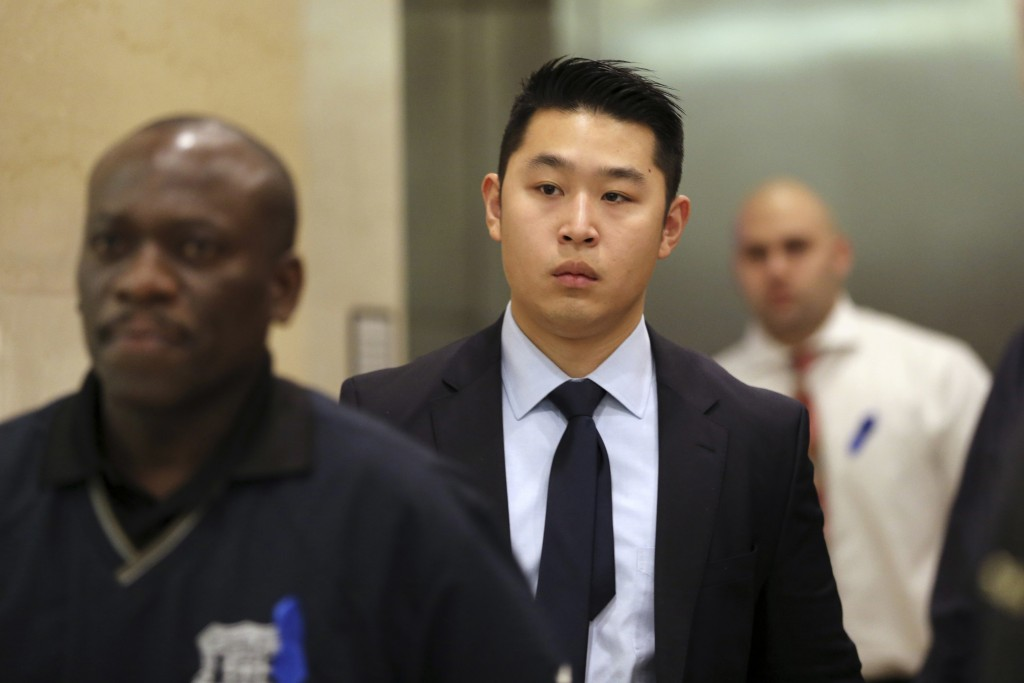 In this Feb. 9 photo, Police officer Peter Liang, center, exits the courtroom during a break in closing arguments in his trial. (AP Photo/Mary Altaffer, File)