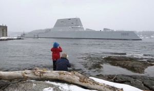 Dave Cleaveland and his son, Cody, photograph the USS Zumwalt as it passes Fort Popham at the mouth of the Kennebec River in Phippsburg, Maine, as it heads to sea for final builder trials. (AP Photo/Robert F. Bukaty, File)