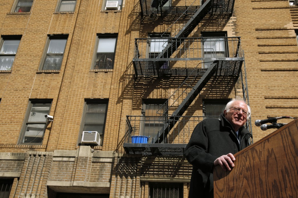 U.S. Democratic presidential candidate and U.S. Senator Bernie Sanders speaks at a campaign rally on the street outside his childhood home (rear) in Brooklyn, New York April 8, 2016. REUTERS/Brian Snyder