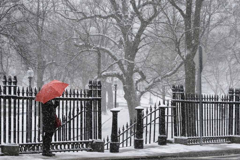 A pedestrian with an umbrella waits in the snow during a spring snow storm in Boston, Massachusetts April 4, 2016. REUTERS/Brian Snyder