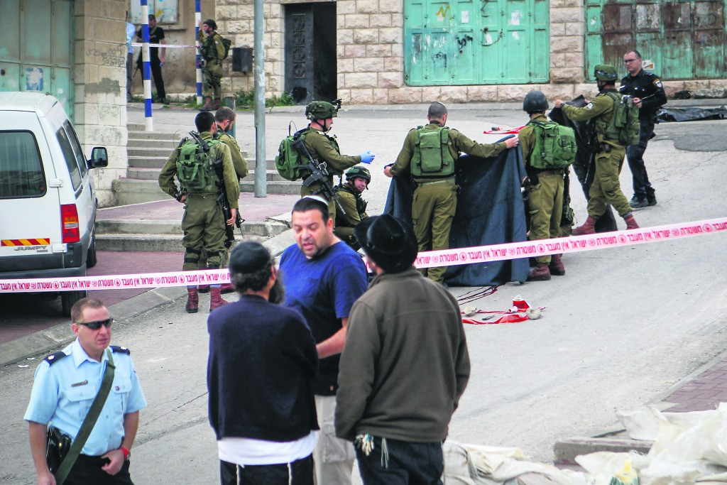 Israeli soldiers remove the body of a Palestinian man who stabbed a soldier in the West Bank city of Hebron on March 24, 2016. The Palestinian was shot at the scene after stabbing and lightly wounding an Israeli soldier. Photo by Wissam Hashlamon/Flash90 *** Local Caption *** טרור פיגוע דקירה פצוע קל מחבל מת גופה חיילים חברון