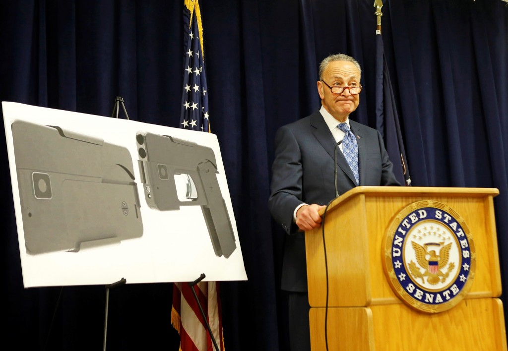 U.S. Sen Charles Schumer, (D-New York), stands beside two photographs of what appears to be a cellphone, but is actually a handgun, during a press conference in his office in New York on Monday. (AP Photo/Kathy Willens)