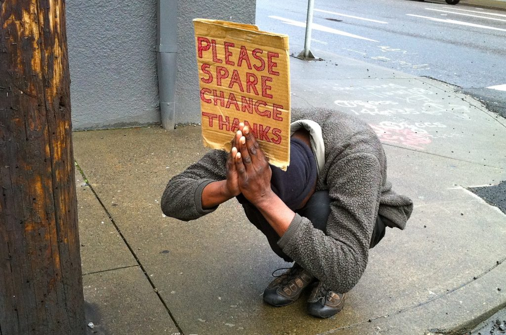 A panhandler in Portland, Oregon, takes on a prayerful pose to entice motorists to donate spare change.