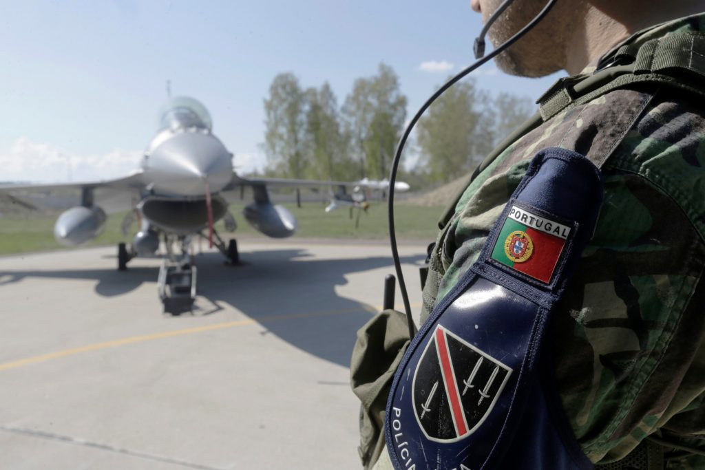 Portugal's Air Force military police officer guards F-16 fighter during the NATO Baltic air policing mission rotation event in Siauliai, Latvia. (Ints Kalnins/Reuters)