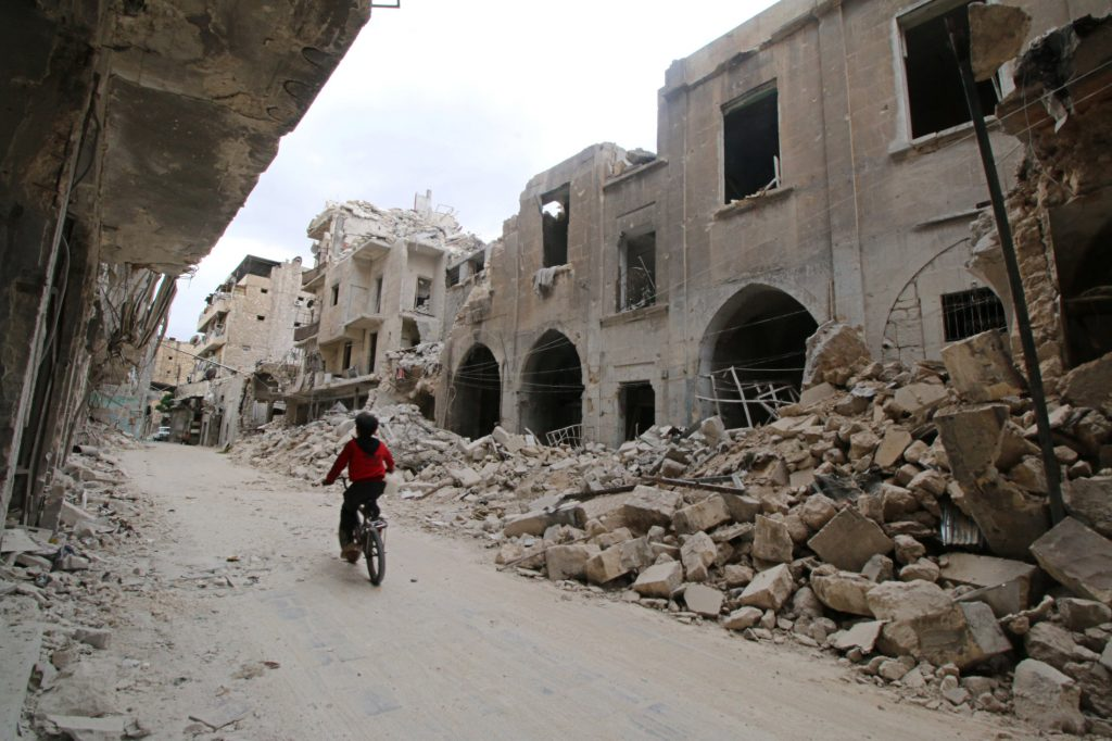 A boy rides a bicycle near damaged buildings in the rebel-held area of Old Aleppo, Syria, on Thursday. (Reuters/Abdalrhman Ismail)