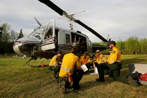 An Alberta wildfire firefighter crew holds a meeting in front of their helicopter while waiting on stanby to respond to new wildfires at a helipad in Lac la Biche, Alberta, Canada. (Chris Wattie/Reuters)