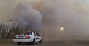 A helicopter is seen through heavy smoke near a Royal Canadian Mounted Police (RCMP) vehicle as a large wildfire burns in and around Ft McMurray, Alberta, Canada. (RCMP/Handout via Reuters)
