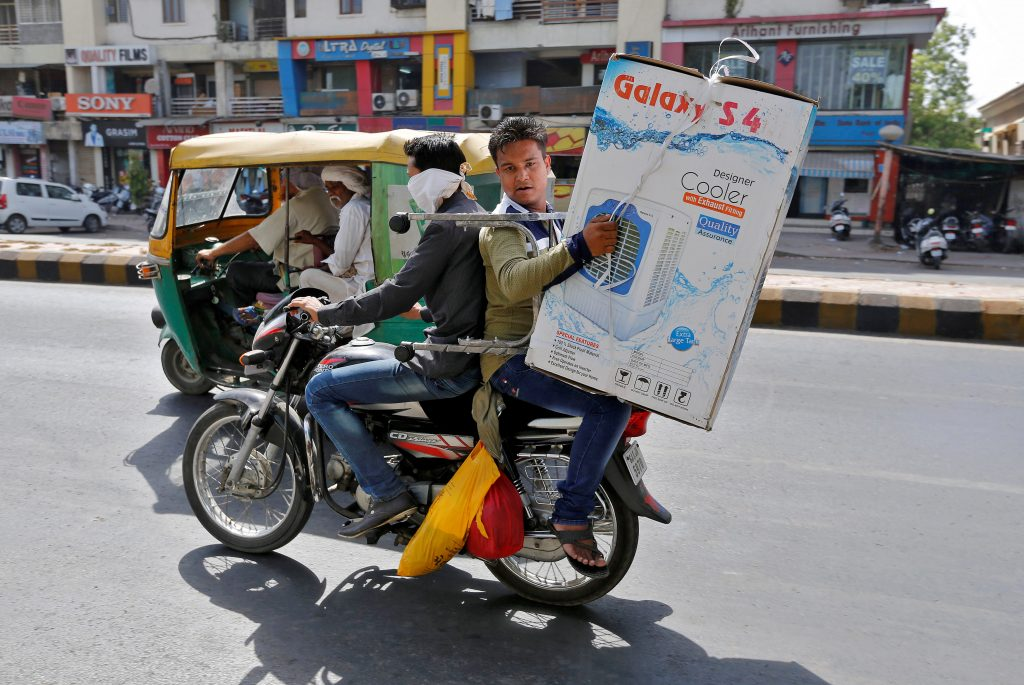 A man carries an air cooler on the back of a motorbike in Ahmedabad, India, on Friday. (Reuters/Amit Dave)