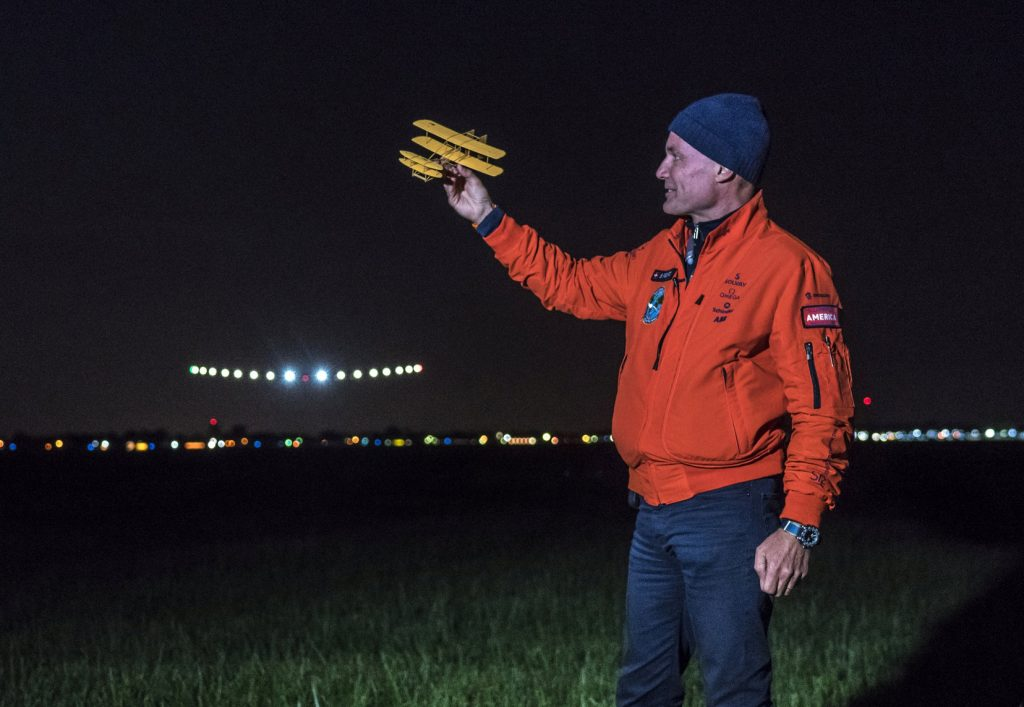 Bertrand Piccard, holding a historical model of a plane designed by the Wright brothers, welcomes the Solar Impulse 2 (Si2), piloted by Andre Borschberg, at Dayton International Airport in Ohio on Saturday night. (Andre Borschberg, Jean Revillard, Christophe Chammartin/SI2/Handout via Reuters)