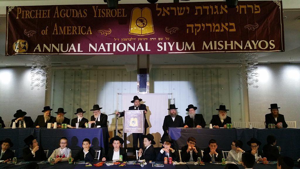 "Rabbi Ephraim Levi, National Director of Pirchei Agudas Yisroel of America, addresses the 53rd annual Siyum Mishnayos on Sunday. Over 1,100 boys attended the Siyum Mishnayos al shem Harav Yehoshua Silbermintz, zt""l, at the Kol Yaakov Hall in Flatbush. Other speakers included Rabbi David Ozeiry, Rabbi Chaim Krauss, and Rabbi Labish Becker. The event was chaired by Rabbi Fischel Schachter, and Kaddish was recited by Mr. Abe Eisner. (Hillel Engel/Agudas Yisroel of America)"