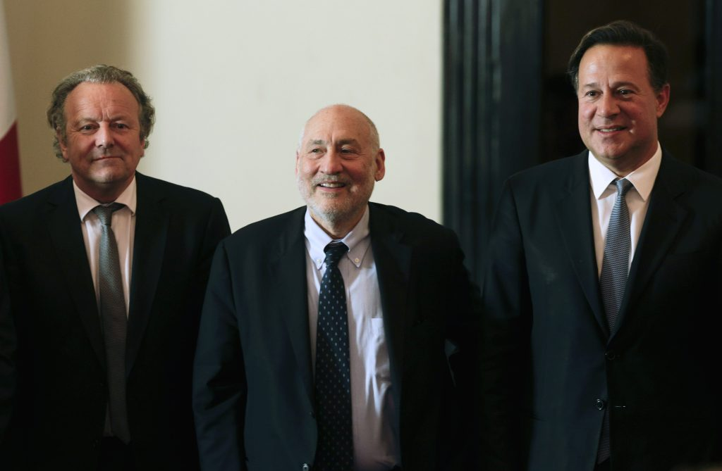 ADDS STIGLITZ'S SURNAME - Panama's President Juan Carlos Varela, right, poses for a photo with Nobel economics laureate Joseph Stiglitz, center, and Mark Pieth, a professor of criminal law and criminology at the University of Basel, in Panama City, Friday, April 29, 2016. The government of Panama has established a committee of independent experts to make recommendations on cleaning up the country's financial system, after leaks of documents from the Panamanian law firm Mossack Fonseca caused an international uproar over offshore accounts. The advisory group includes Stiglitz and Pieth. (AP Photo/Arnulfo Franco)
