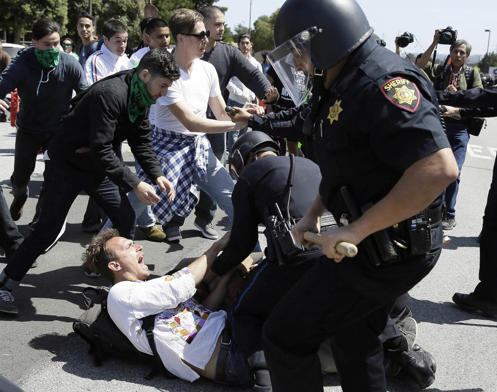 Police arrest a man who was protesting Donald Trump outside the Hyatt Regency hotel during the California Republican Party 2016 Convention in Burlingame, Calif., on Friday. (AP Photo/Eric Risberg)