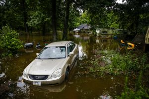 A car and home sit in flood water from Spring Creek along North Ravenswood Drive, in Magnolia, Texas. (Michael Ciaglo/Houston Chronicle via AP)