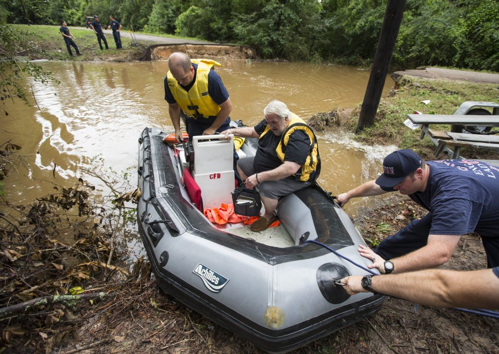 Conroe firefighters evacuate Jim Treadway via boat after Treadway was stranded when Pecan Bend Road was washed out near the San Jacinto River, in Conroe, Texas. (Brett Coomer/Houston Chronicle via AP)