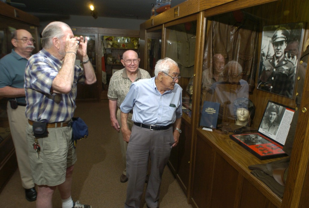 In this June 27, 2006 photo, World War II veterans Frederick Mayer (right); Richard Gottleber (second from right); and John Billings (second from left), inspect Gottleber's display at Michigan's Own Military and Space Museum in Frankenmuth, Mich. Stan Bozich of the museum is at left. (AP Photo/The Saginaw News, David A Sommers)