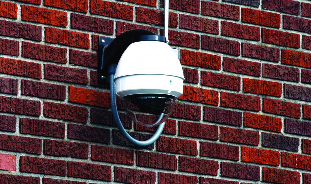 FILE - A security camera hangs on the side a School. (AP Photo/Rick Bowmer)