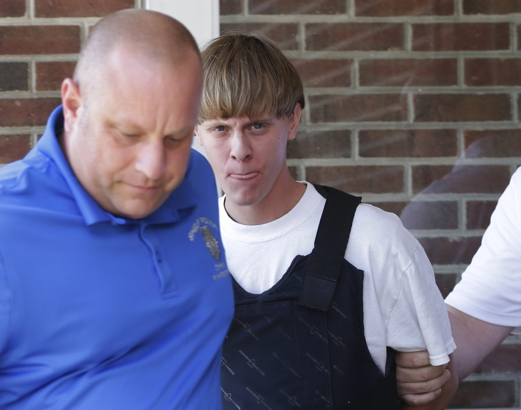 Dylann Roof, shown here as he is  escorted from the Shelby, N.C., police department, after his arrest on June 18. (AP Photo/Chuck Burton, File)