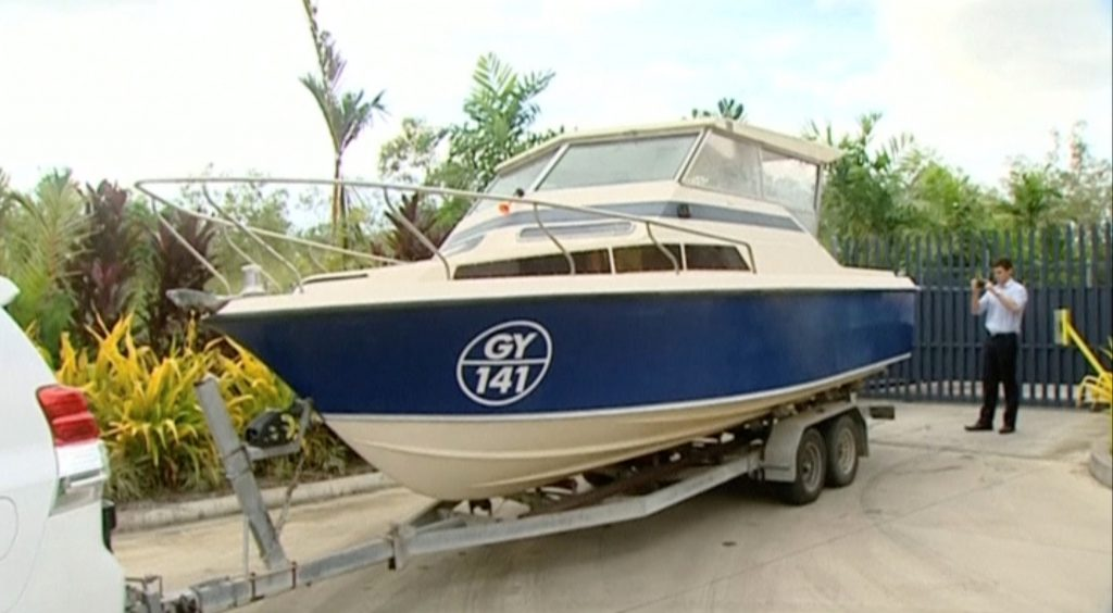 An officer takes pictures of a boat, which Australian police have seized in Cairns, Queensland, Australia in this still image taken from video, May 11, 2016. Australian police have detained five men suspected of planning to sail a small boat from the far north to Indonesia and the Philippines en route to joining Islamic State in Syria, officials said on Wednesday. Australian Broadcasting Corporation/Handout via REUTERS TV TPX IMAGES OF THE DAY ATTENTION EDITORS - THIS PICTURE WAS PROVIDED BY A THIRD PARTY. EDITORIAL USE ONLY. NO RESALES. NO ARCHIVE. AUSTRALIA OUT. NO COMMERCIAL OR EDITORIAL SALES IN AUSTRALIA