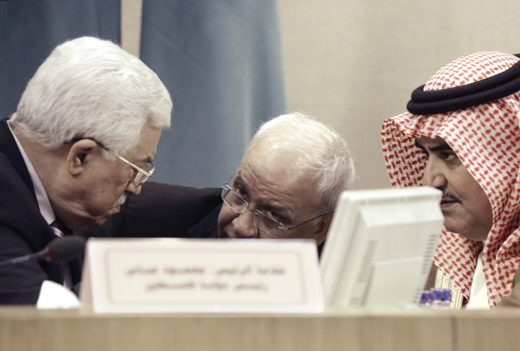 Palestinian President Mahmoud Abbas, left, and Bahrain's Foreign Minister Khalid bin Ahmed al-Khalifa listen to Palestinian chief negotiator Saeb Erikat during an emergency Arab League session in Cairo where they voted to support the Paris peace conference. (AP Photo/Amr Nabil)