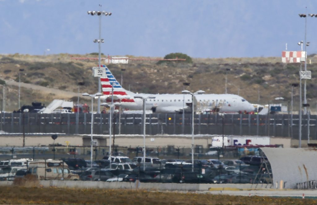 """An American Airlines jet sits on a remote stretch of runway at Los Angeles International Airport Tuesday, as it is screened for a """"non-credible"""" threat. (AP Photo/Damian Dovarganes)"""