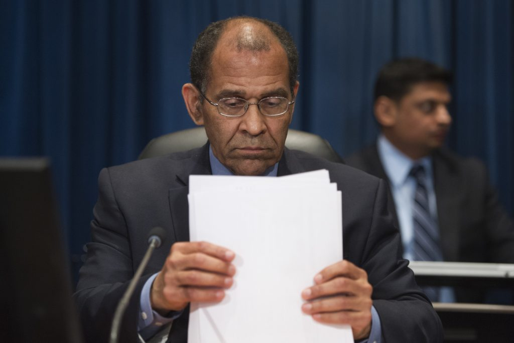 National Transportation Safety Board (NTSB) Chairman Christopher Hart, gathering papers at the conclusion of an NTSB meeting in Washington on Tuesday, to determine the cause of the derailment of an Amtrak passenger train in Philadelphia last year. (AP Photo/Cliff Owen)