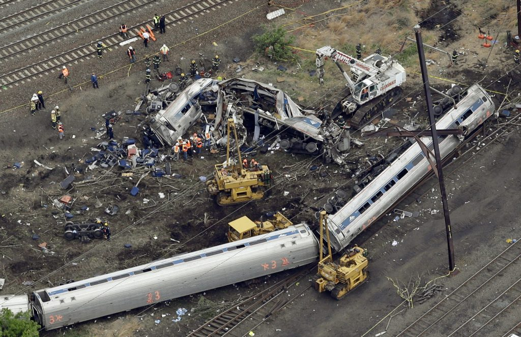 FILE- In this Wednesday, May 13, 2015 file photo, emergency personnel work at the scene of a Tuesday night derailment in Philadelphia of an Amtrak train headed to New York. The National Transportation Safety Board is scheduled to meet Tuesday, May 17, 2016, to detail the probable cause of last year's fatal derailment. (AP Photo/Patrick Semansky, File)