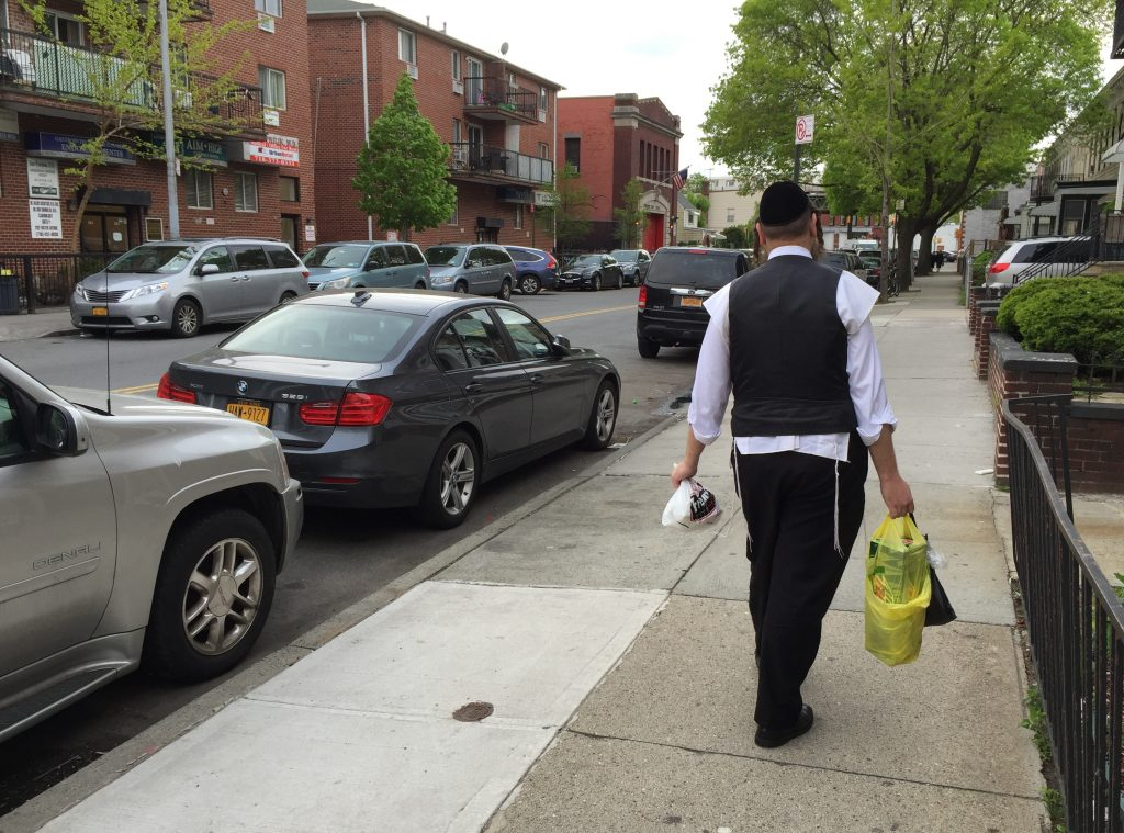 A man carried grociery bags on Foster Ave. in Brooklyn on Thursday. (Isser Berg/Hamodia)