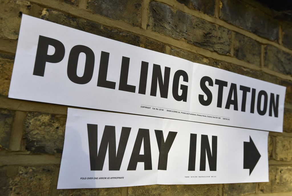 A sign on a wall points to the entrance of a polling station for the London mayoral elections, in west London, Britain May 5, 2016. REUTERS/Toby Melville