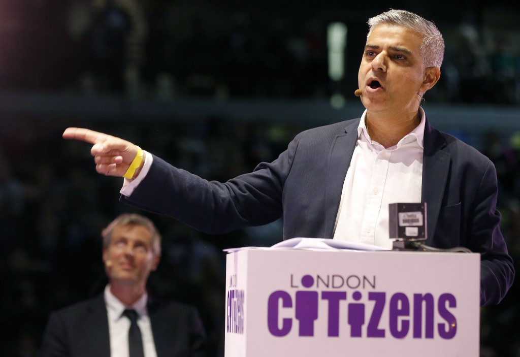 In this April 28, 2016 photo, Candidate for London Mayor Sadiq Khan speaks while Zac Goldsmith, left, listens during an assembly at the London Mayor election event of London Citizens in London. In the race to become London's next mayor, one candidate is a bus driver's son who grew up in social housing, the other a billionaire's son raised in a mansion. They are two very different London success stories, and one is about to become mayor of Europe's largest city. The contrast between Labour's Sadiq Khan and Conservative candidate Zac Goldsmith is resonant in a city where soaring property prices are increasing income disparities. (AP Photo/Frank Augstein)