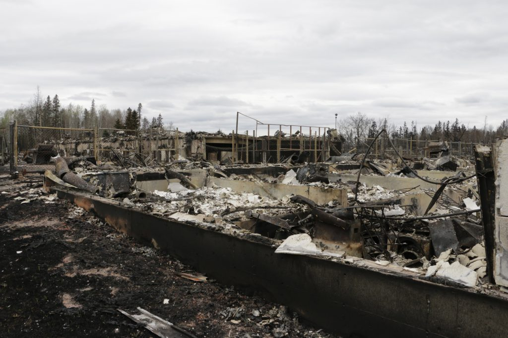 CORRECTS ATTRIBUTION- Destroyed townhouses in the Abasand neighborhood of Fort McMurray, Alberta, are viewed after a massive wildfire, Monday, May 9, 2016. A break in the weather has officials optimistic they have reached a turning point on getting a handle on the massive wildfire. (AP Photo/Rachel La Corte)