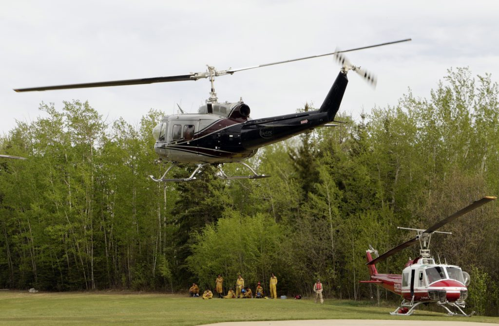 A helicopter carrying Agriculture and Forestry firefighters returning from a patrol mission takes off after refueling at a helipad in Lac La Biche, Alberta, on Saturday, May 7, 2016. The firefighters in Lac La Biche are focusing on recent wildfires that have broken out since the one at Fort McMurray. (AP Photo/Rachel La Corte)