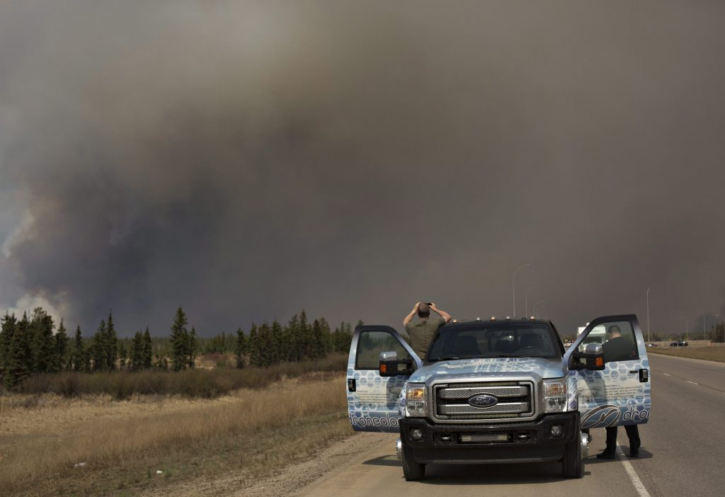 People stop to take photos of a wildfire south of Fort McMurray, Alberta, on Thursday, as they evacuate the area. (Jason Franson/The Canadian Press via AP)
