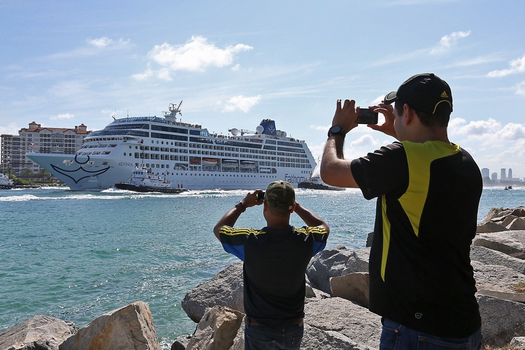 People take photos as Adonia leaves port in Miami, Sunday, May 1, 2016, en route to Cuba. After a half-century of waiting, passengers finally set sail on Sunday from Miami on an historic cruise to Cuba. Carnival's Cuba cruises, operating under its Fathom band, will visit the ports of Havana, Cienfuegos and Santiago de Cuba. (Patrick Farrell/The Miami Herald via AP) MAGS OUT; MANDATORY CREDIT