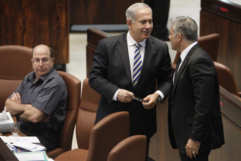 israeli Defense Minister Moshe 'Boogie' Ya'alon looks over at Israeli Prime Minister Benjamin Netanyahu speaking with Israeli Finance Minister Yair Lapid during a plenum session in the Israeli parliament on June 05, 2013. Photo by Miriam Alster/FLASH90 *** Local Caption *** øàù äîîùìä áðéîéï ðúðéäå îìéàä áéáé éàéø ìôéã ùø äàåöø ùø äáèçåï áåâé éòìåï