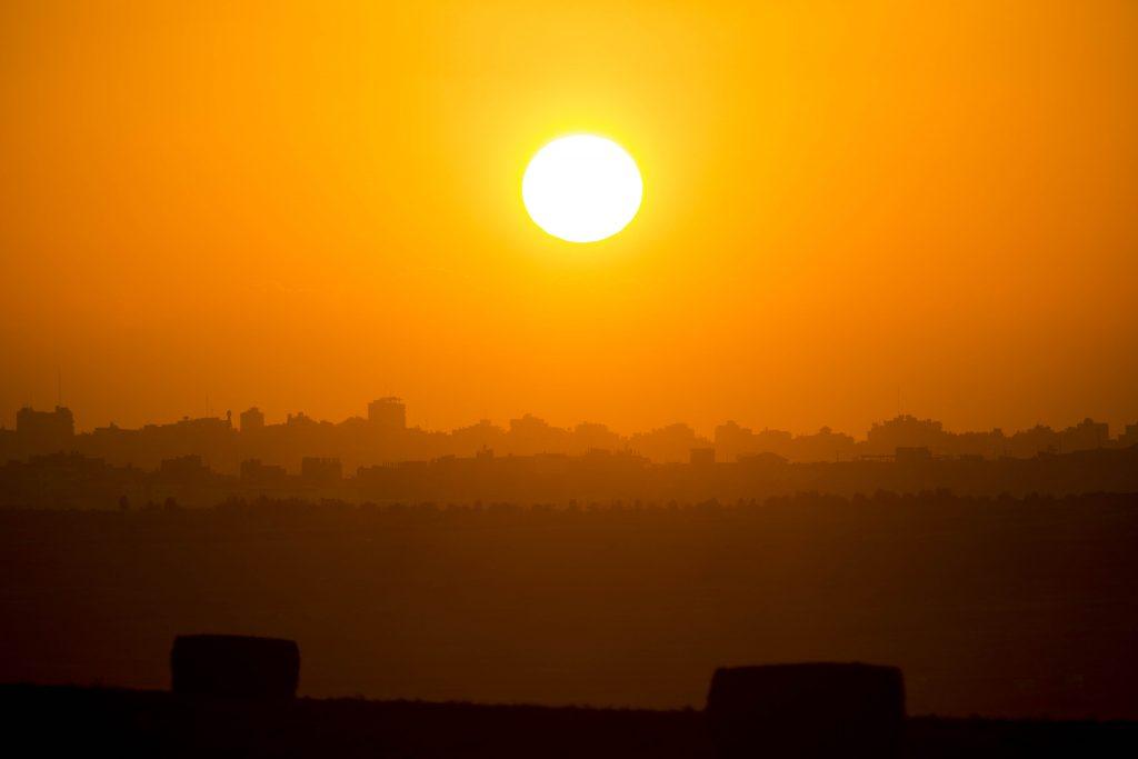 """The sun sets over the Gaza Strip, on August 2, 2014, Hamas claimed responsibility on Saturday for a deadly Gaza Strip ambush in which an Israeli army officer have been captured. Photo by Yonatan Sindel/Flash90 *** Local Caption *** éùøàìéí éùøàìé öåôéí îáöò öå÷ àéúï òæä øöåòú òæä îáöò öå÷ àéúï öä""""ì ãøåí ù÷éòä"""