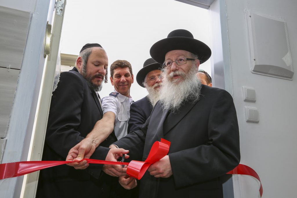 Minister of Health Yaakov Litzman cuts the rope during a ceremony for a new Magen David Adom (Red Star of David) medical station in Beitar Illit, May 3, 2016. Photo by Yaakov lederman/Flash90