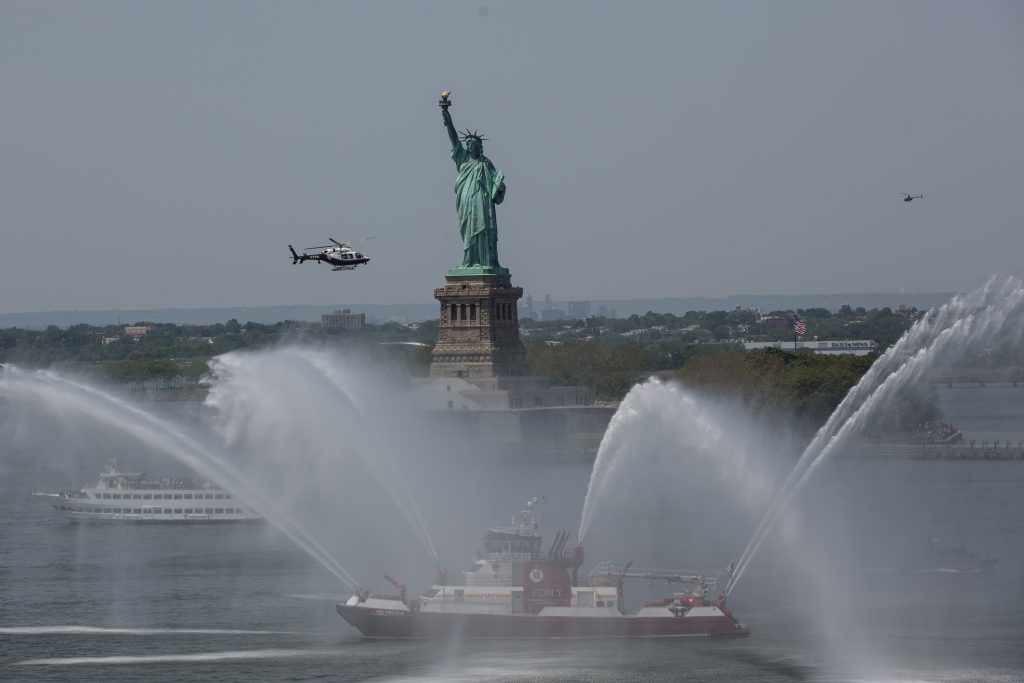 A flotilla of U.S. Navy ships, back-dropped by the Statue of Liberty, are welcomed to New York for Fleet Week with a ceremonial spray. (Office of Mayor de Blasio)