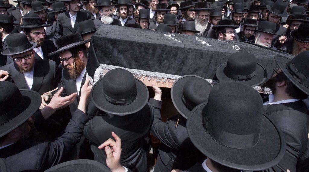 Mourners carry the aron of Rav Yitzchak Rosenberg at the levaya in Williamsburg on Wednesday. (AP Photo/Mark Lennihan)