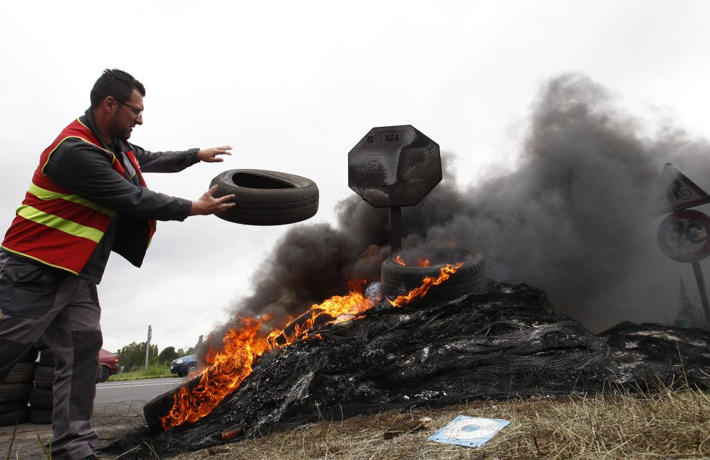 A CGT (General Confederation for Work) union member burns tires at the blockade of a fuel depot in Douchy-les-Mines on Friday.  (AP Photo/Michel Spingler)