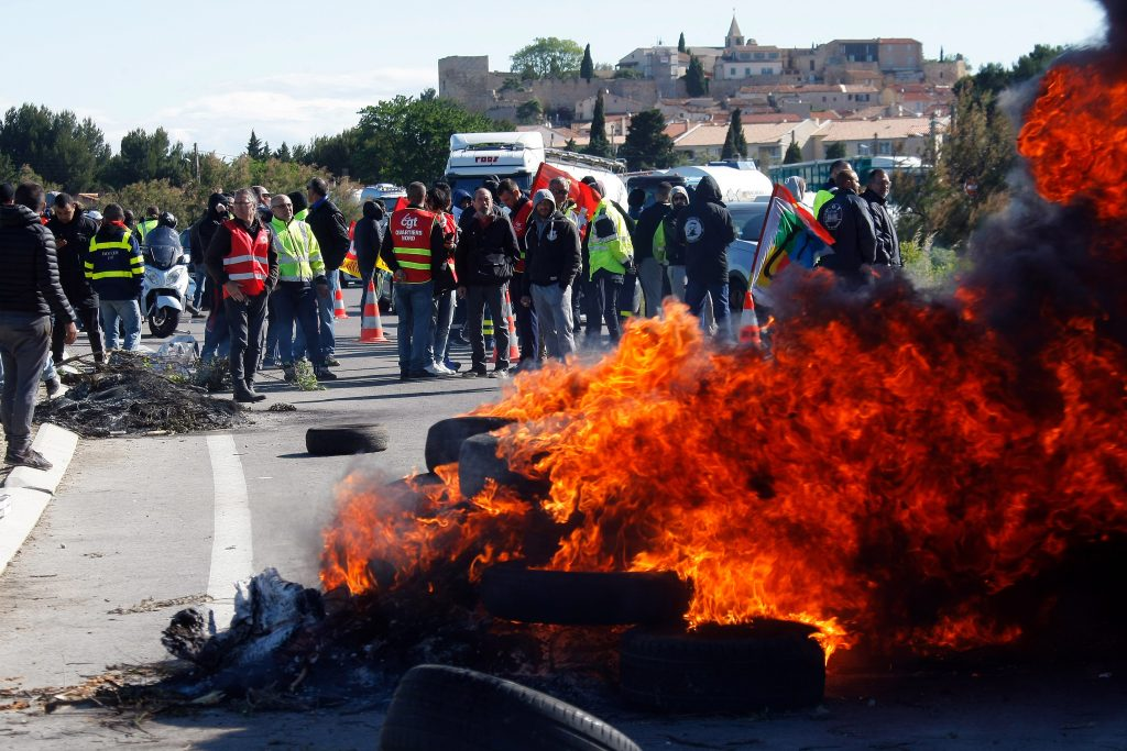Union members on strike stand near a burning barricade preventing the access to a refinery in Fos sur Mer, southern France, on Monday. (AP Photo/Claude Paris)