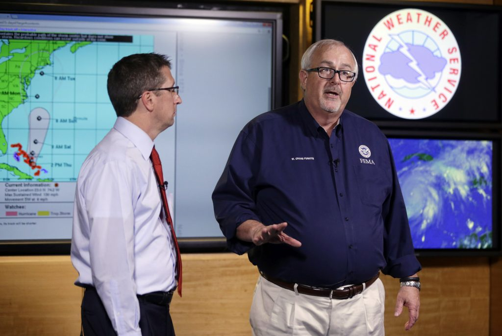 FILE- In this Oct.1, 2015 file photo, Craig Fugate, Administrator of the Federal Emergency Management Agency (FEMA), right, talks about the status of Hurricane Joaquin as it moves through the eastern Bahamas as Rick Knabb, Director of the National Hurricane Center, left, participate in a media briefing at the National Hurricane Center. The U.S. government is set to release its forecast for how many hurricanes and tropical storms are expected to form over Atlantic and Caribbean waters in the next six months. It's an annual reminder from the National Oceanic and Atmospheric Administration that coastal living comes with significant risks. (AP Photo/Lynne Sladky, File)