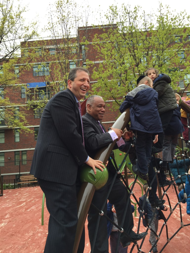 NYC Councilman Brad Lander (left) and Parks Commissioner Mitchel Silver join children on a new wall ladder in the renovated Dome Playground. (Isser Berg/Hamodia)