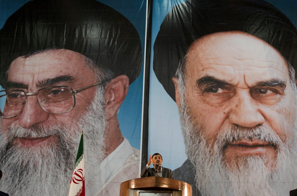 Iranian President Mahmoud Ahmadinejad stands under pictures of Iran's Supreme Leader Ayatollah Ali Khamenei (L) and Iran's late leader Ayatollah Ruhollah Khomeini while speaking during a ceremony to mark Khomeini's death anniversary at his tomb at Tehran's Behesht-Zahra cemetery June 3, 2011. REUTERS/Morteza Nikoubazl/File Photo