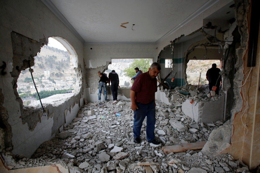 Palestinians inspect the apartment of Palestinian assailant Zaid Amer, who is held in an Israeli prison, after it was destroyed by Israeli troops in the West Bank city of Nablus May 3, 2016. REUTERS/Abed Omar Qusini
