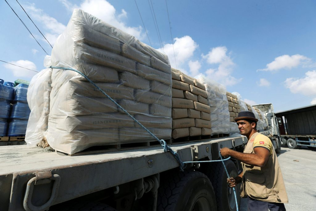 A Palestinian man stands next to a truck loaded with bags of cement at the Kerem Shalom crossing between Israel and southern Gaza Strip May 23, 2016. REUTERS/Ibraheem Abu Mustafa