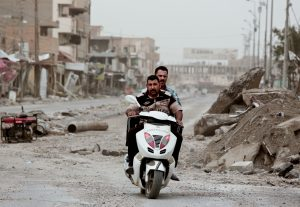 Policemen ride a motorbike near Haji Ziad Square in the city of Ramadi, Iraq, on March 20. (AP Photo/Maya Alleruzzo)
