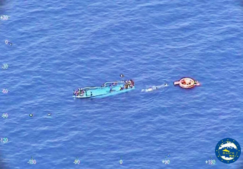 People ask for help after their boat overturned off the Libyan coast Thursday, May 26, 2016. A migrant boat sank off Libya's coast Thursday with about 100 passengers on board. Officials said 88 people had been rescued and that some 20 bodies were spotted in the sea. (EUNAVFORMED via AP)