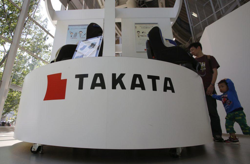 Visitors look at child seats manufactured by Takata Corp. at an automaker's showroom in Tokyo. (AP Photo/Shizuo Kambayashi)